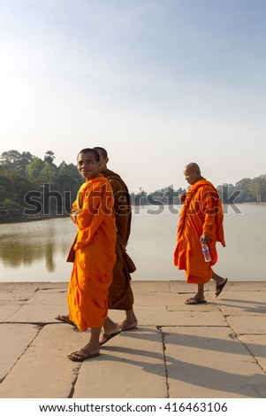 ANGKOR, CAMBODIA - FEBRUARY 3: Three smiling Cambodian monks dressed in orange and walking toward Angkor Wat temple with the pond in the background. UNESCO heritage site, Cambodia 2016