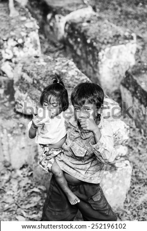 ANGKOR THOM, CAMBODIA - SEP 27, 2014: Unidentified local boy holds his little sister on her arms at one of the temple of Angkor Thom. Angkor Thom was the last capital city of the Khmer empire