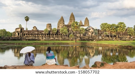 Angkor Wat and girls look on sunset - stock photo