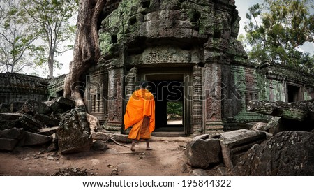 Angkor Wat monk. Ta Prohm Khmer ancient Buddhist temple in jungle forest. Famous landmark, place of worship and popular tourist travel destination in Asia - stock photo