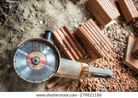 Angle grinder used on construction site for cutting bricks, debris. Tools and bricks on new building site - stock photo