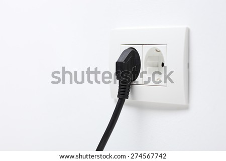 Angle shot of a black electric cord plugged into a plastic socket on a plain white wall - stock photo