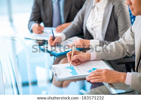 Angle view of a business team analyzing business documents while meeting  - stock photo