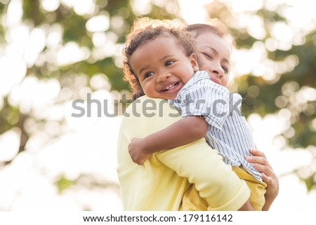 Angle view of a mom bonding his little cheerful son on the foreground  - stock photo