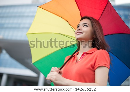 Angle view of a young girl standing under the parasol in the city
