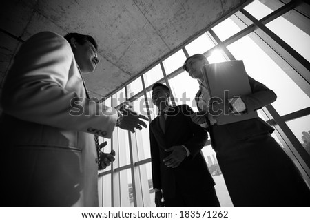 Angle view of business colleagues talking at the end of business meeting  - stock photo