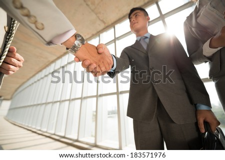 Angle view of business partners handshaking in the sign of successful dealing  - stock photo