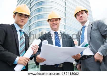 Angle view of constructor workers with drafts in hands smiling and looking at camera - stock photo
