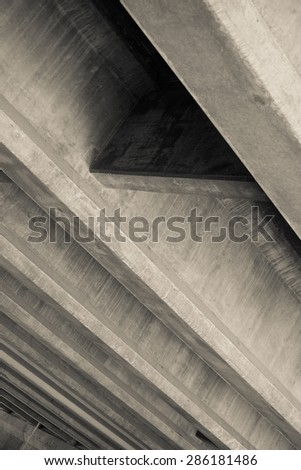 Angled cement lines of overpass. - stock photo