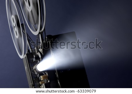 Angled 16mm movie projector projecting images through smoky background with space for copy - stock photo