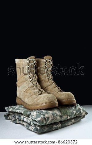 Angled photo of a pairr of tan leather Army combat boots placed together on camouflage uniform on black background - stock photo