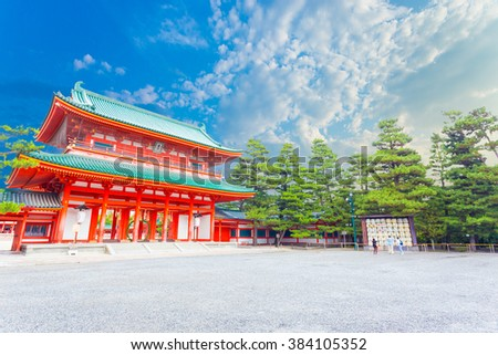 "Angled red Tower Gate, Ro-Mon at the main outer chinowa-kuguri decorated entrance of Heian Jingu Shinto Shrine on a beautiful, blue sky day in Kyoto, Japan  (Foreign text: ""Donated by"") - stock photo"
