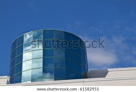 Angled reflective windowed Cylinder Building reflecting blue sky and clouds