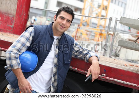 Angled shot of construction worker leaning on a truck - stock photo