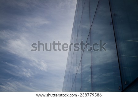 Angled view of a glass wall of an office building with sky reflection. - stock photo