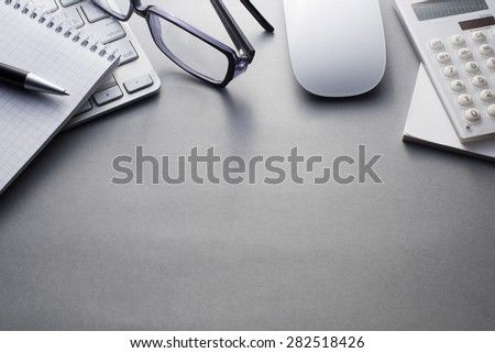 Angled View of Mac Computer Keyboard and Mouse with Various Office Supplies on Grey Desk with Ample Copy Space - stock photo