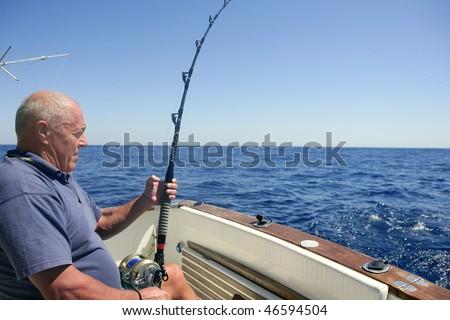 Angler elderly big game sport fishing boat blue summer sea sky - stock photo