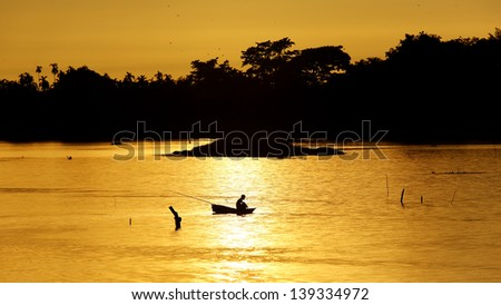 Angler in small boat on  lake - stock photo
