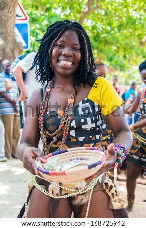 ANGOLA, LUANDA - MARCH 4, 2013: A smiling Angolan woman dances the local folk dance and collects money in Angola, Mar 4, 2013. Music is one of the main African entertainments. - stock photo