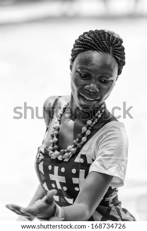 ANGOLA, LUANDA - MARCH 4, 2013:  Angolan beautiful woman dances the national folk dance in black and white in Angola, Mar 4, 2013. Music is one of the main African entertainments. - stock photo
