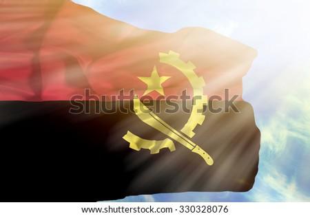 Angola waving flag against blue sky with sunrays - stock photo