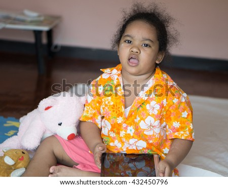 Angry African Asia child playing the tablet. - stock photo