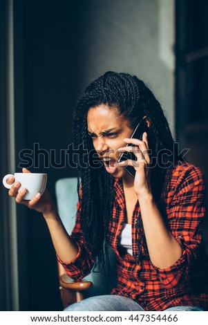 Angry african woman screaming on the mobile phone - stock photo