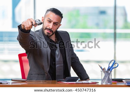 Angry aggressive businessman with gun in the office - stock photo