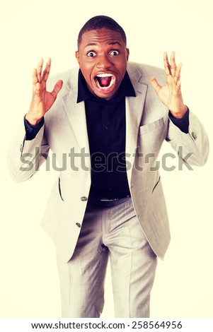 Angry and frustrated african businessman screaming. - stock photo