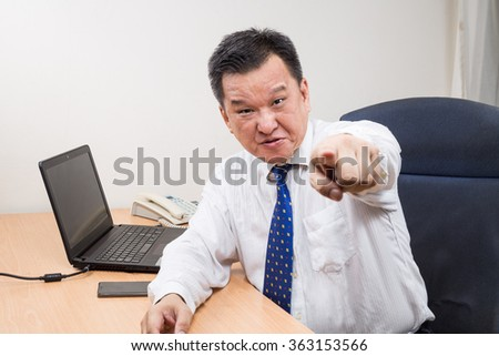 Angry and stressful Asian business manager shouting and pointing behind his desk in office - stock photo