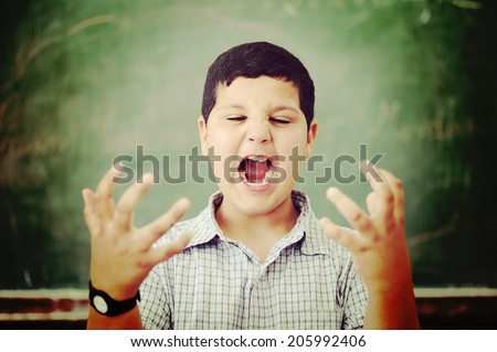 Angry and upset pupil at school classroom - stock photo