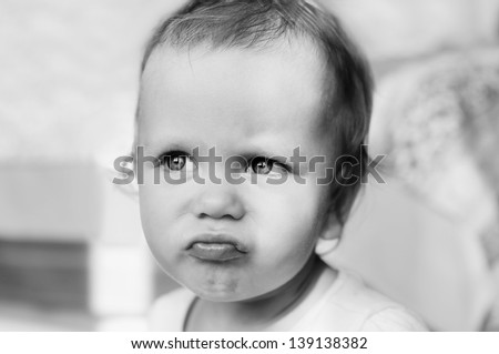 angry baby girl making face in black and white - stock photo