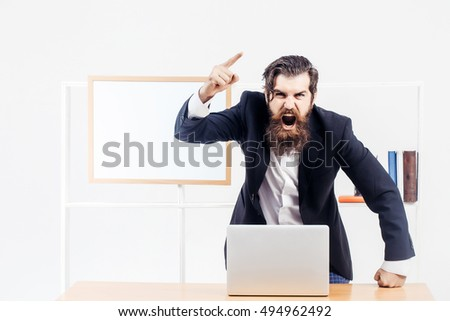 Angry bearded manager in black suit shouts raised his finger up standing near desk with laptop in office