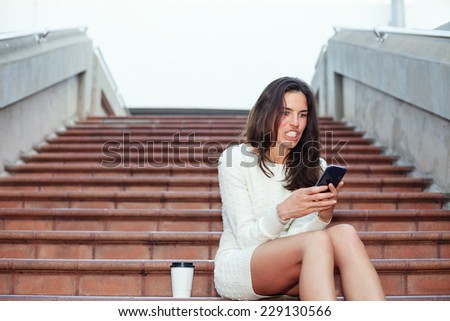 angry beautiful woman sitting on the stairs with mobile phone and cup of coffee - stock photo