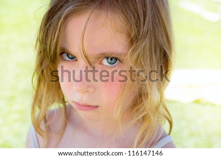 Angry blond children girl portrait looking at camera - stock photo