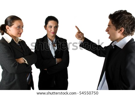 Angry boss businessman screaming and pointing to his colleagues businesswoman who listen him shocked - stock photo