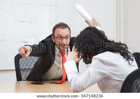 Angry boss firing female colleague by showing the door with his forefinger  - stock photo