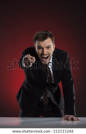Angry boss. Furious young businessman pointing at camera and shouting while isolated on red - stock photo