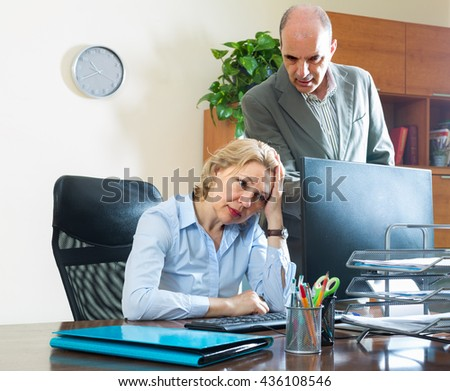 Angry boss scolding careless aged secretary for mistake at office - stock photo