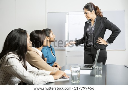 Angry boss talking to her staff during a meeting. Indian business woman.