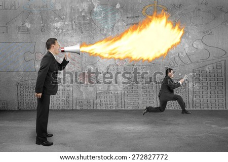 Angry boss using megaphone yelling to employee and spitting fire with business doodles concrete wall background - stock photo