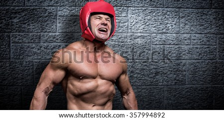 Angry boxer with headgear against grey brick wall - stock photo