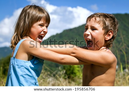 Angry boy and a girl scream and fight with each other outdoors - stock photo