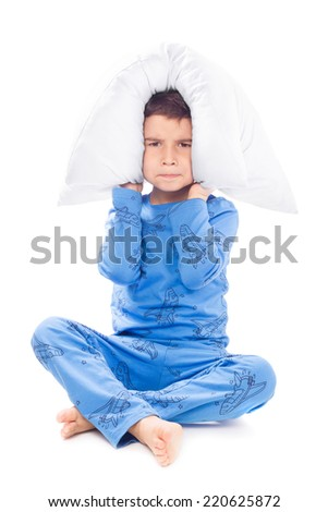 Angry boy covers his ears with a pillow - stock photo