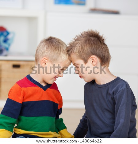 Angry brothers with head to head looking at each other in house - stock photo