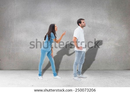 Angry brunette shouting at boyfriend against grey room - stock photo