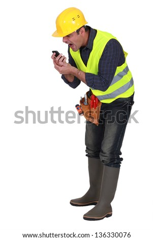Angry builder shouting into telephone - stock photo