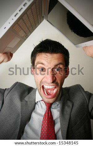 angry business man about to throw his computer against the wall - stock photo