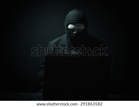 Angry business man as computer hacker in suit stealing data from laptop in front of black background - stock photo