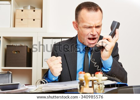 Angry business man screaming at phone in his office - stock photo